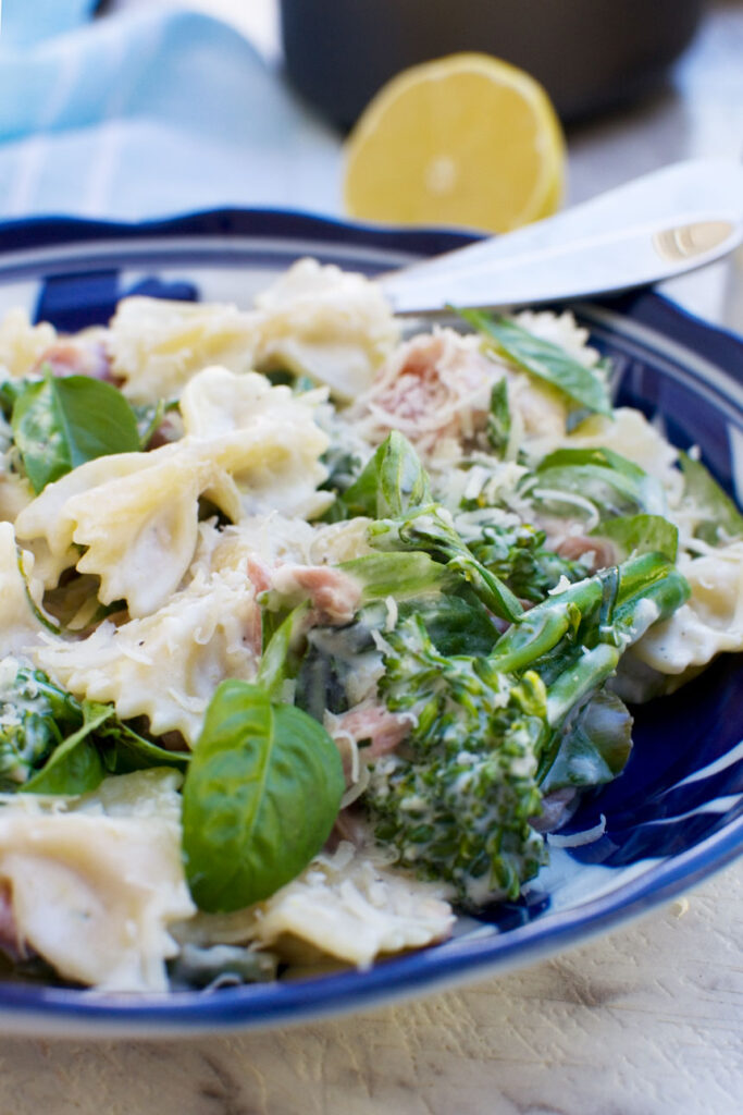 A plate of food with broccoli, with Lemon ricotta pasta and Farfalle with a fork in it
