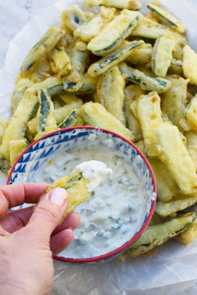 A person dipping a zucchini fry from a big plate into a bowl of tzatziki sauce
