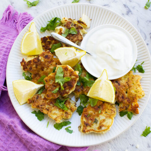A plate of cauliflower fritters on a plate with lemon slices and a purple tea towel in the background