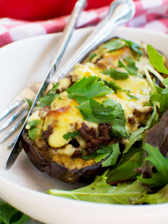 A close up of a white plate of Greek stuffed eggplant or papoutsakia served with a green salad