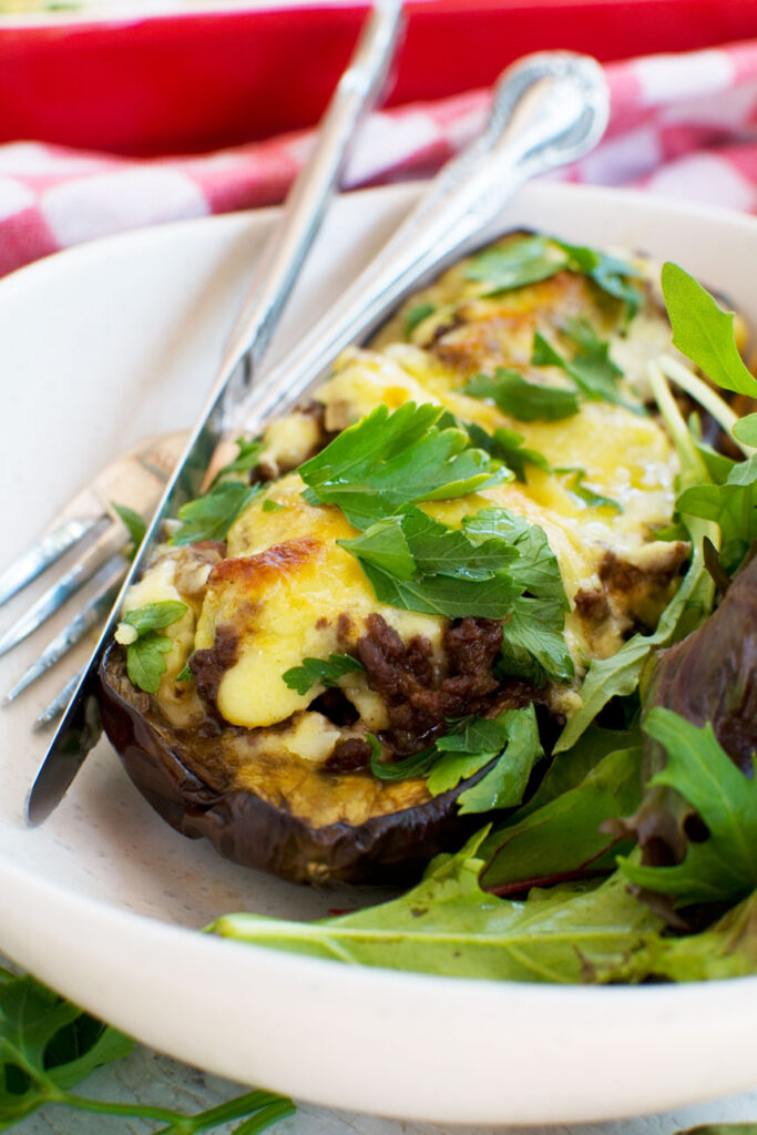 A white plate of Greek stuffed eggplant or papoutsakia served with a green salad