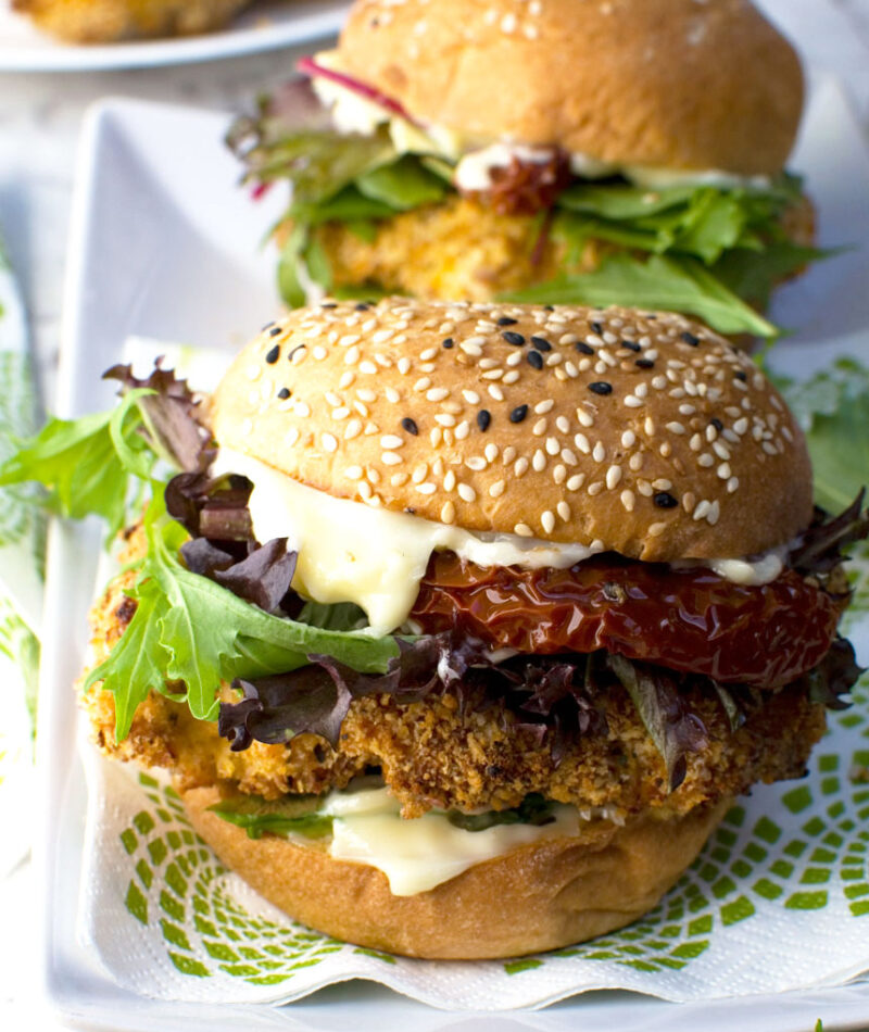 Two crispy chicken burgers on a white plate