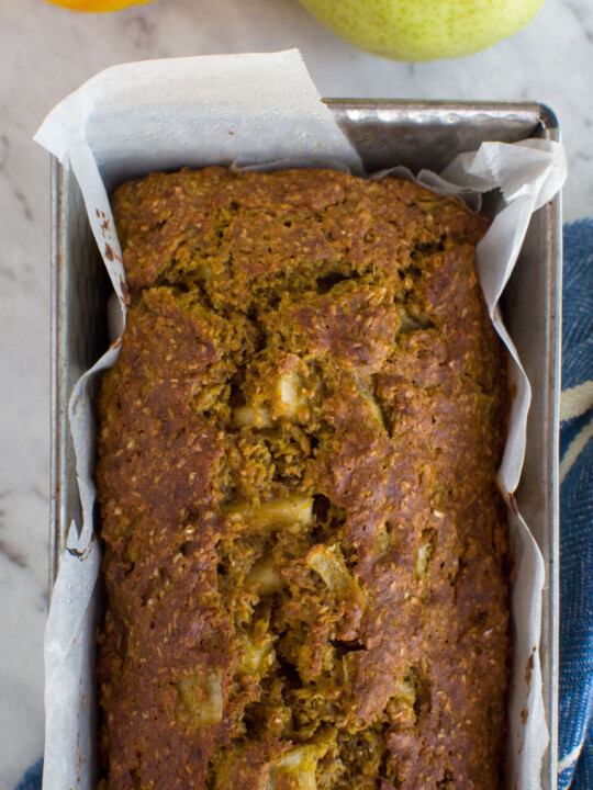 A healthy pumpkin and pear loaf cake in a loaf tin from above