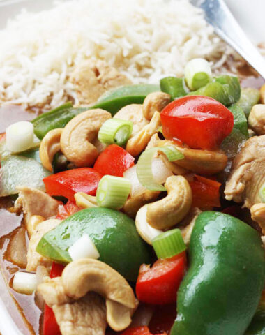 Closeup of chicken cashew nuts and peppers with rice on a rectangular white plate