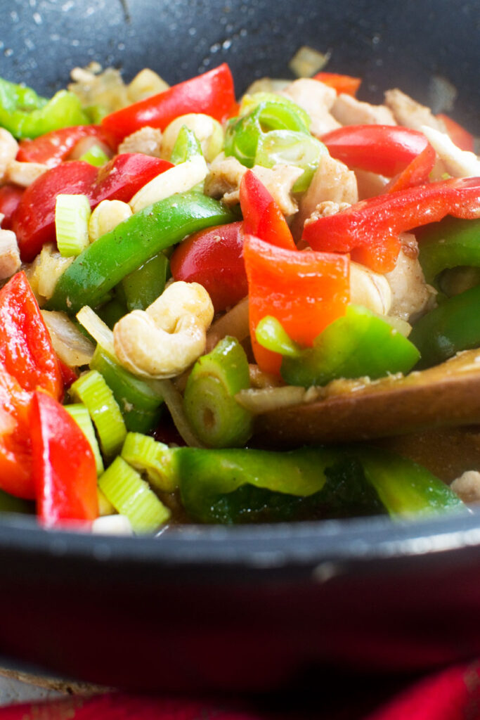A pan of chicken with cashew nuts and peppers