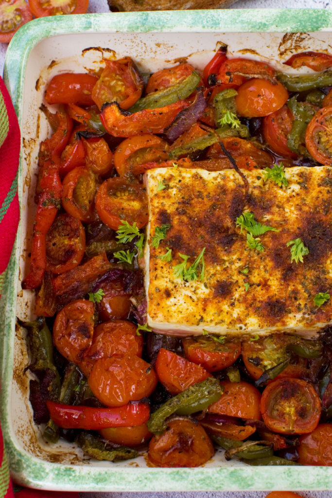 A dish of baked feta with tomatoes, peppers and olives taken from above