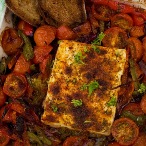 A dish of baked feta with tomatoes, peppers and olives from above