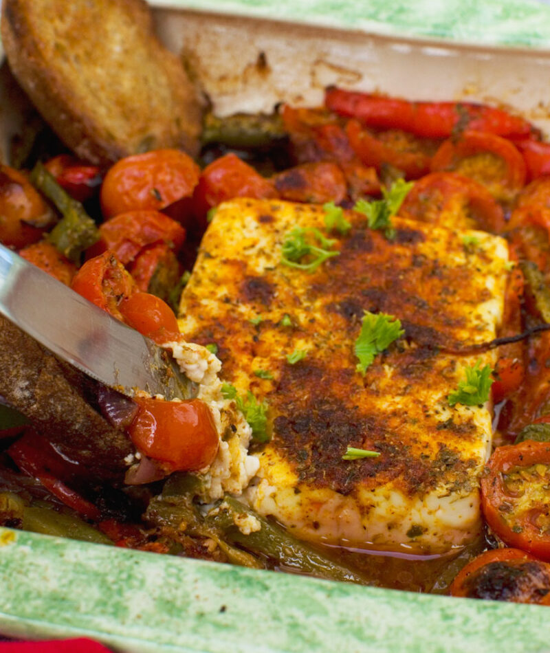 A dish of baked feta with tomatoes, feta and olives
