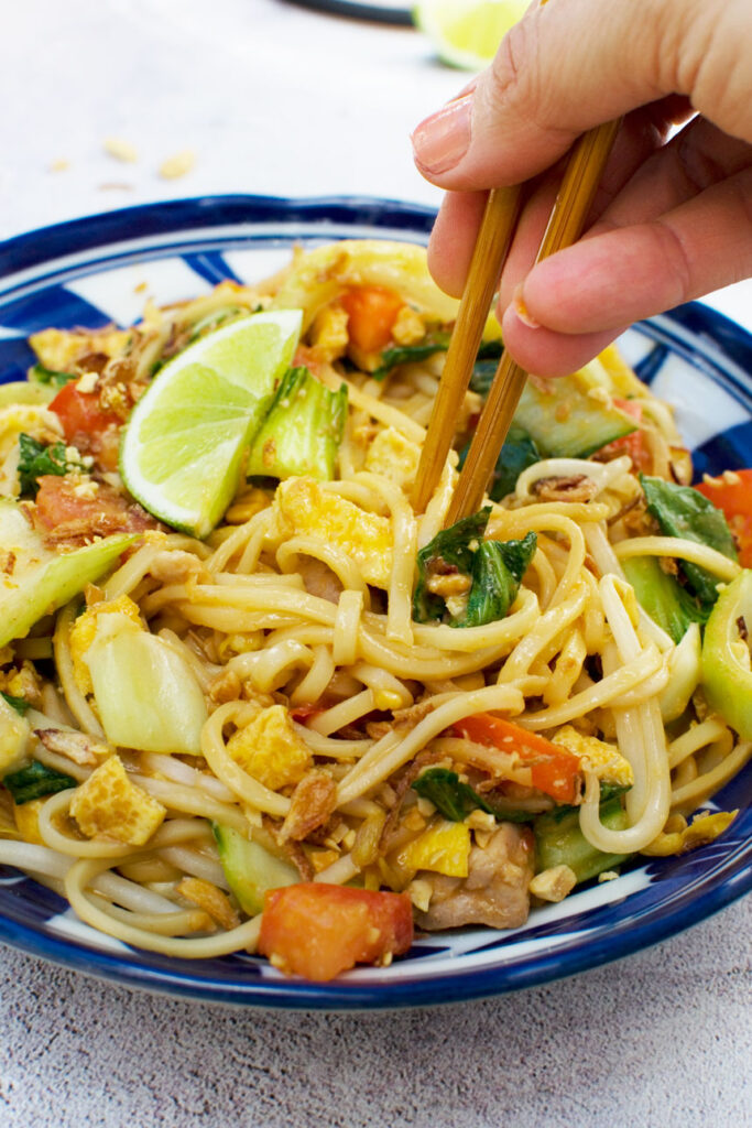 Eating a bowl of mee goreng basah or spicy Indonesian noodles with chopsticks