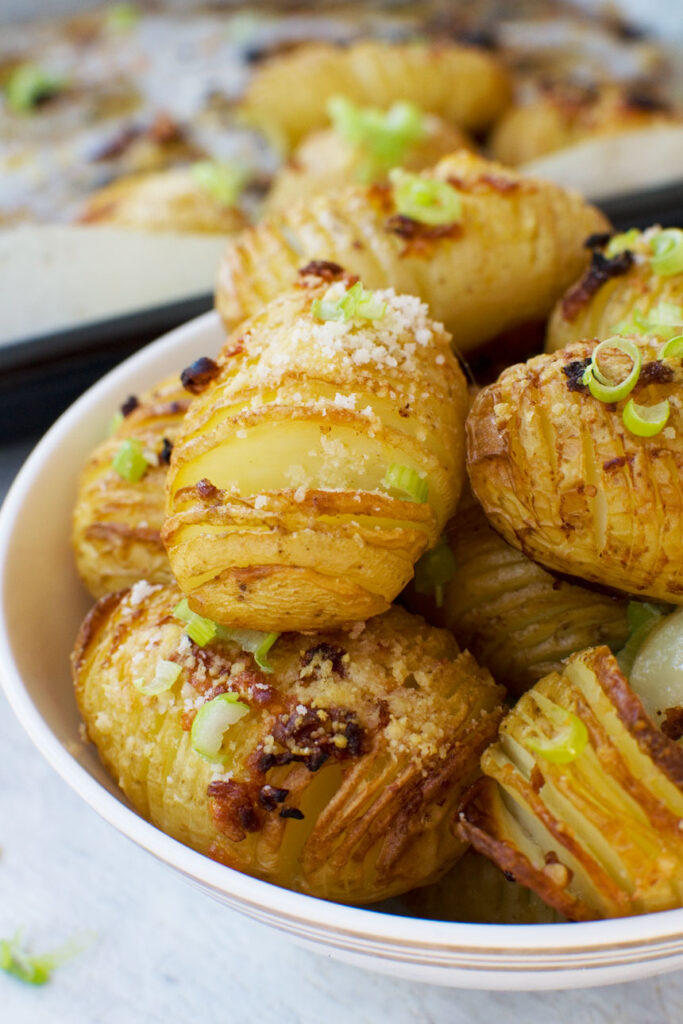 A close-up bowl of mini parmesan and garlic hasselback potatoes
