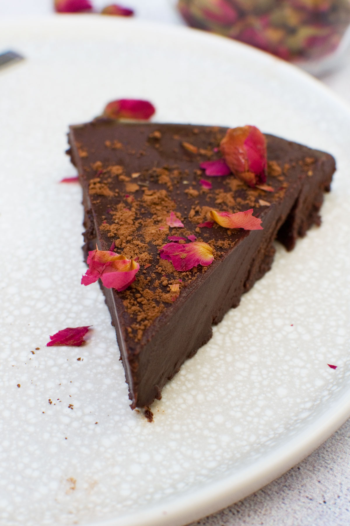 A slice of no bake chocolate truffle cake on a plate decorated with rose buds