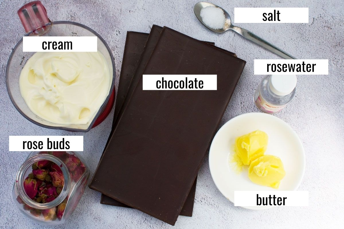 An image showing 6 ingredients for making a no bake chocolate truffle cake: cream, chocolate, butter, salt, rose buds, salt, rosewater