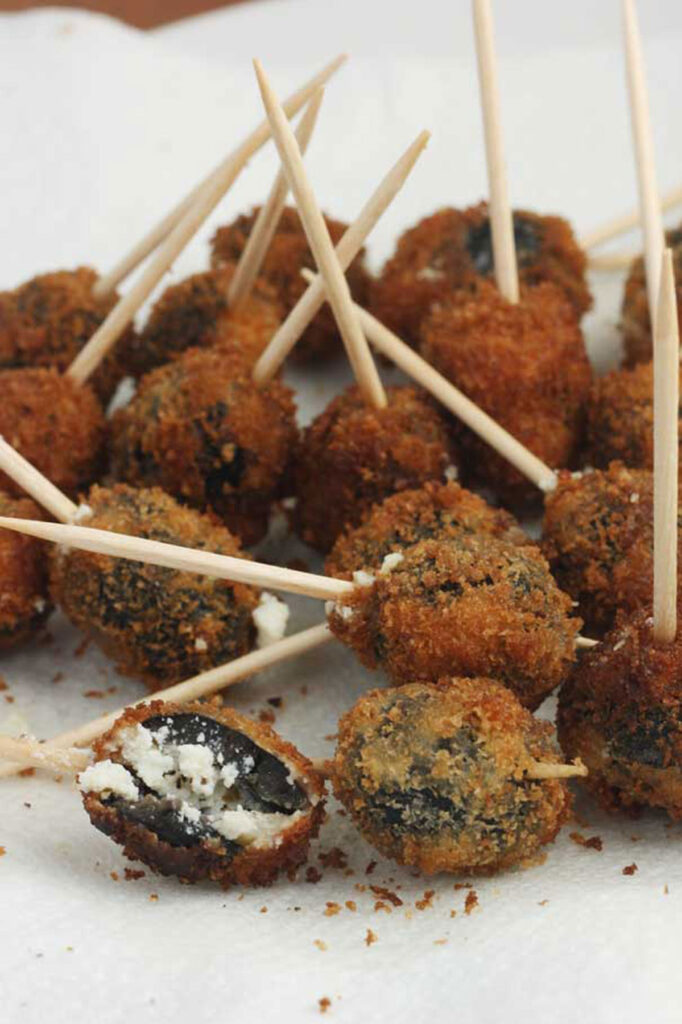 A plate of Greek fried olives with a cocktail stick in them on baking paper on a white plate