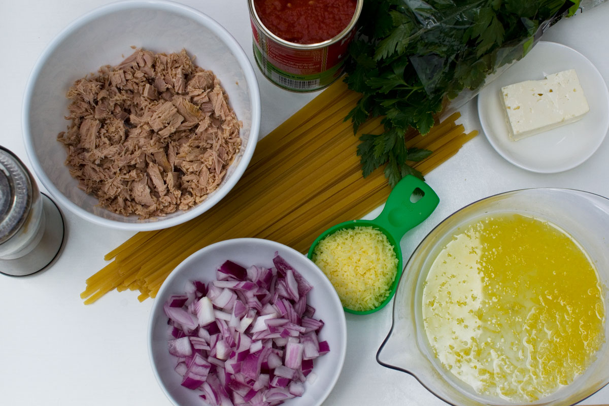A photo showing the main ingredients for lemony tuna spaghetti: tuna, onion, tomatoes, spaghetti, lemon, parmesan, feta, pepper