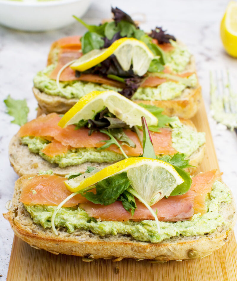 4 smoked salmon bruschettas with smashed avocado and feta on a wooden chopping board
