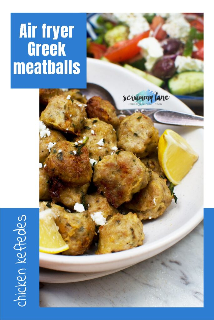 A plate of Greek air fryer chicken meatballs with lemon and feta and a spoon in it - there's the edge of a Greek salad in the background