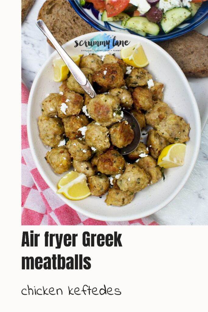 A dish of Greek air fryer meatballs or chicken keftedes from above with lemon and feta and a Greek salad in the background