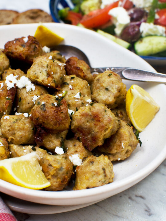 A bowl of Greek air fryer chicken meatballs with slices of lemon and a spoon in - there's also a Greek salad in the background