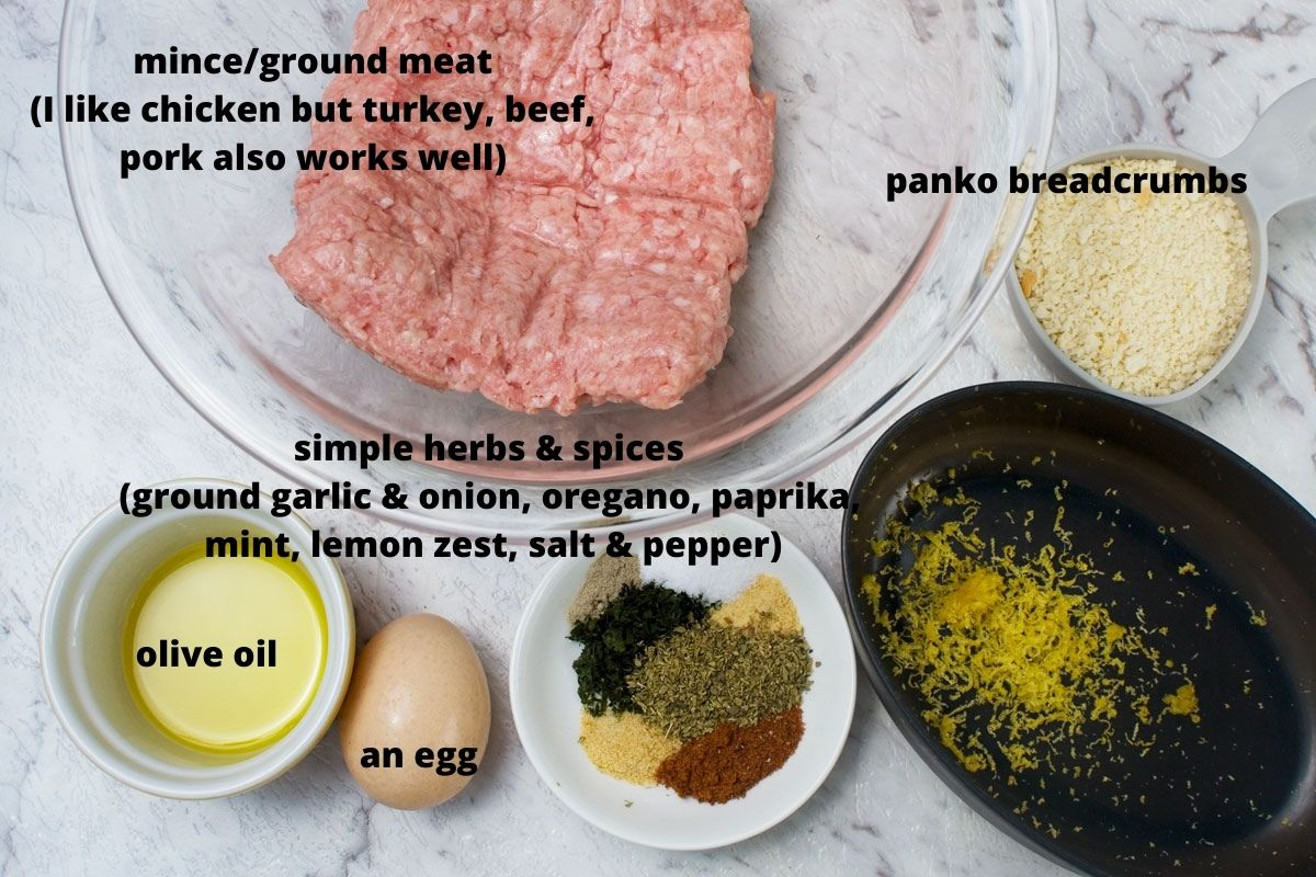 Labelled ingredients for making air fryer Greek meatballs or chicken keftedes: ground chicken, panko breadcrumbs, olive oil, an egg, herbs and spices and lemon zest