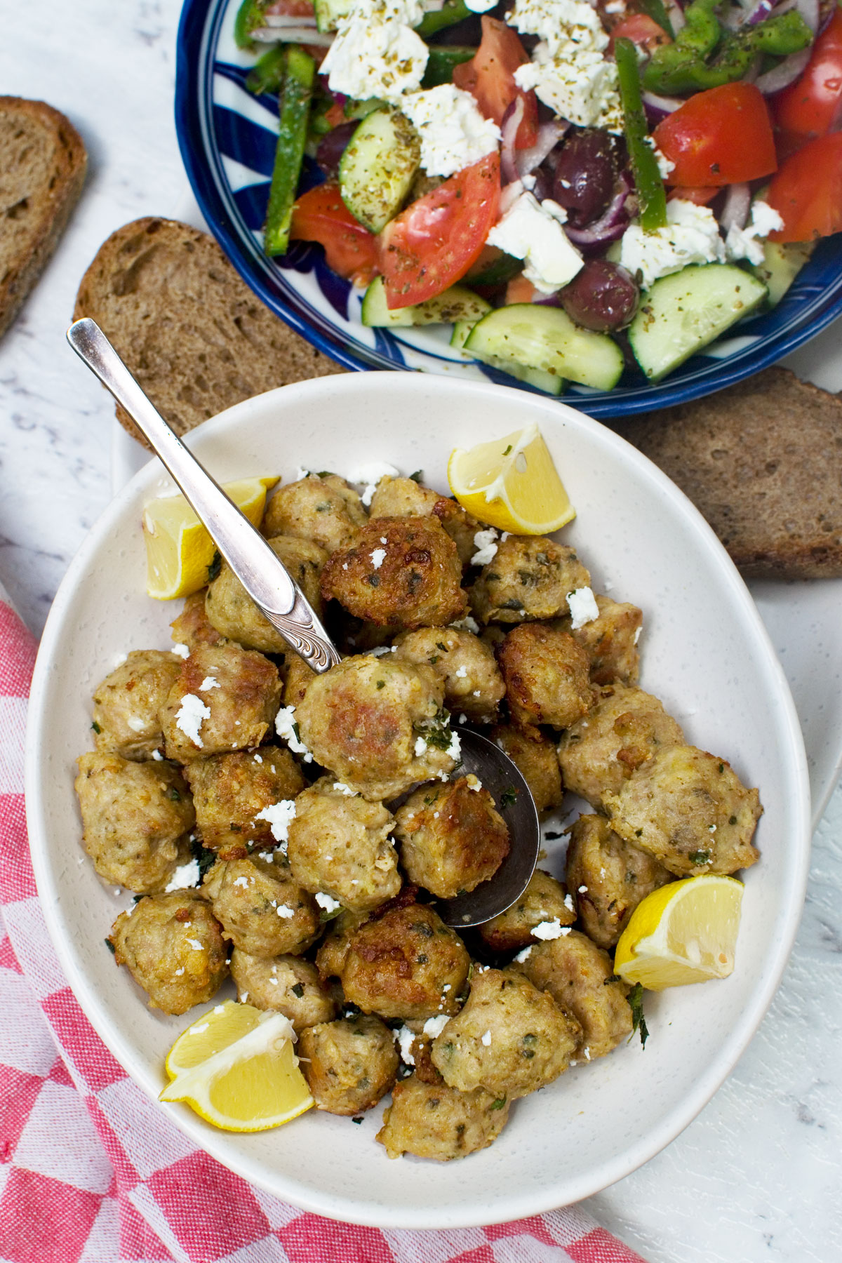 A plate of air fryer Greek meatballs from above with a spoon in and with a Greek salad in the background