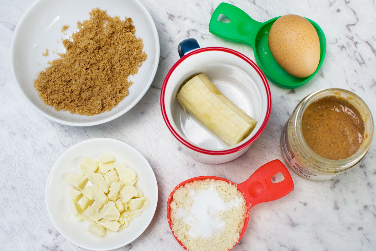 Ingredients to make a gluten free mug cake with banana, almond and white chocolate: brown sugar, 1/2 a banana, white chocolate, almond flour and baking soda, almond butter and an egg