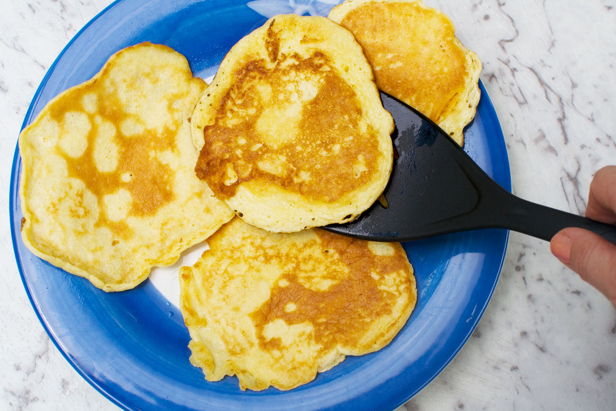 4 pancakes on a blue plate - someone is lifting one off the plate with a black spatula
