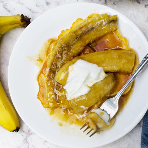 Caramelised banana pancakes with a fork and 2 bananas to the left