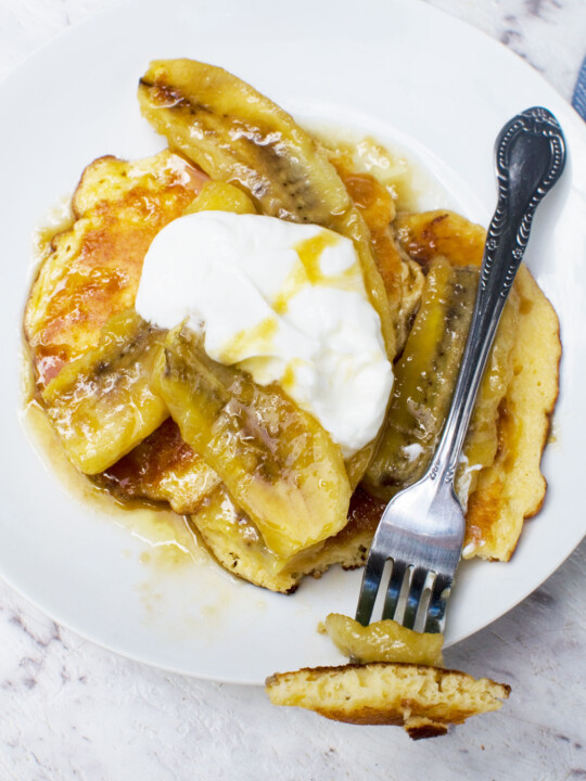 A plate of caramelised banana pancakes from above on a marble background - there's also a fork with a mouthful of pancake on it
