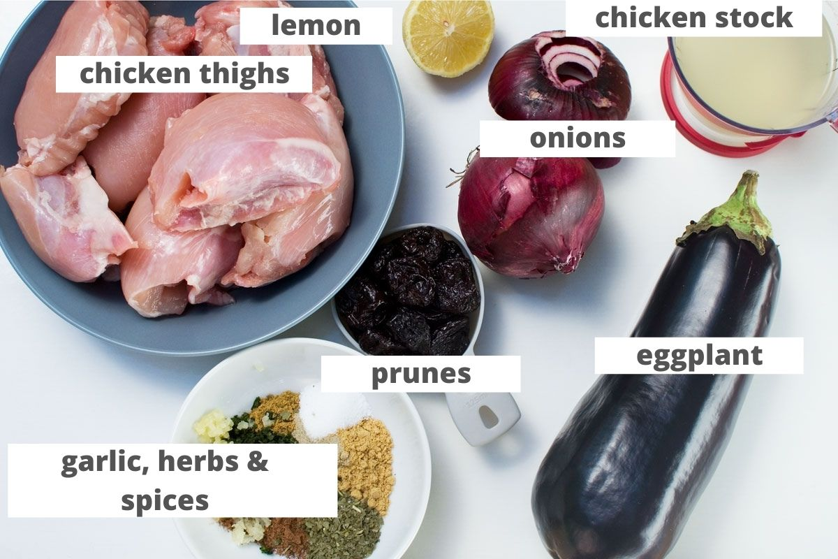 Ingredients to make a Moroccan chicken stew or chicken tagine: chicken thighs, lemon, chicken stock, onions, eggplant, prunes, and garlic, herbs and spices