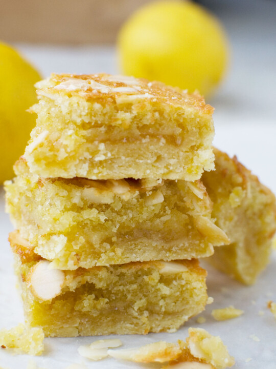 A stack of three lemon bakewell slices with lemons in the background