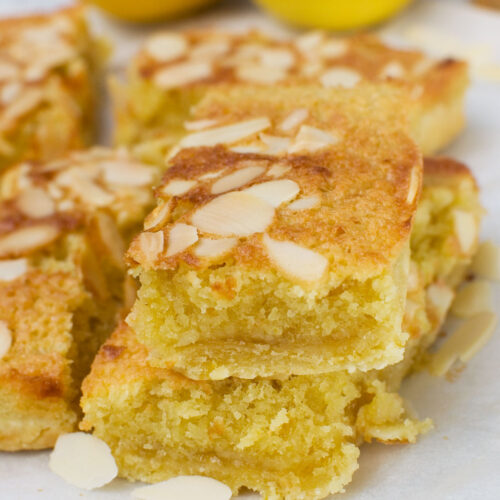 A stack of two lemon bakewell slices with more in the background and lemons