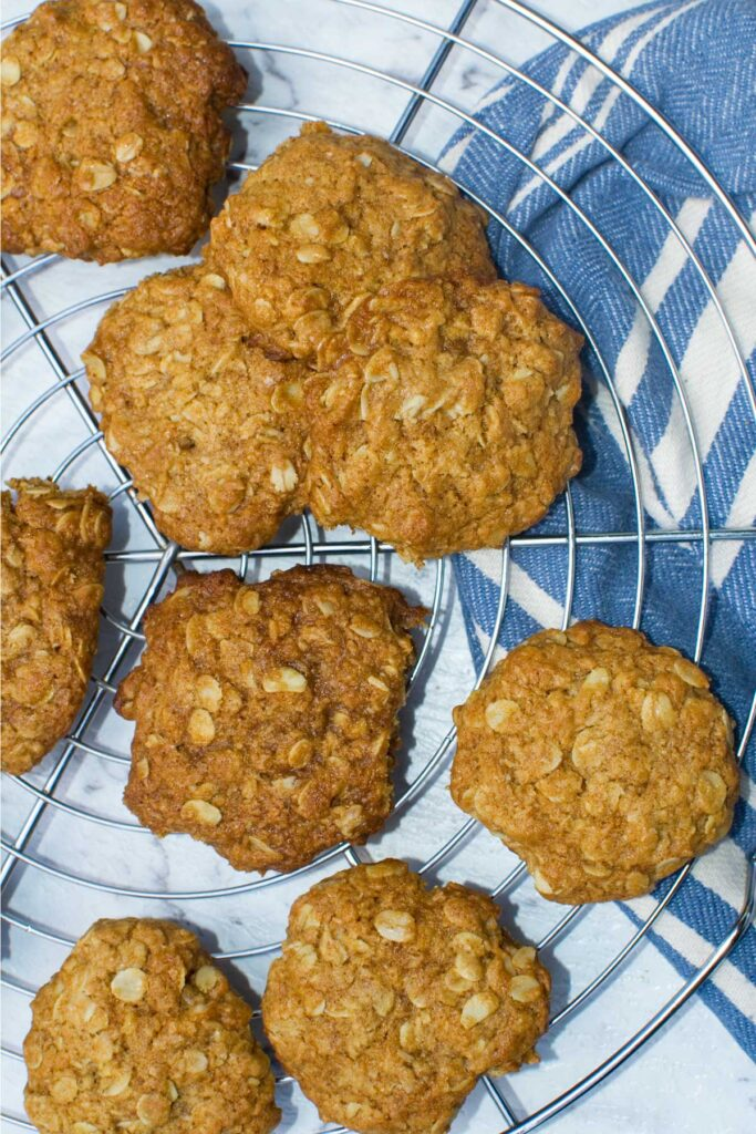 Anzac biscuits on a wire cooling rack from above with a blue tea towel in the background