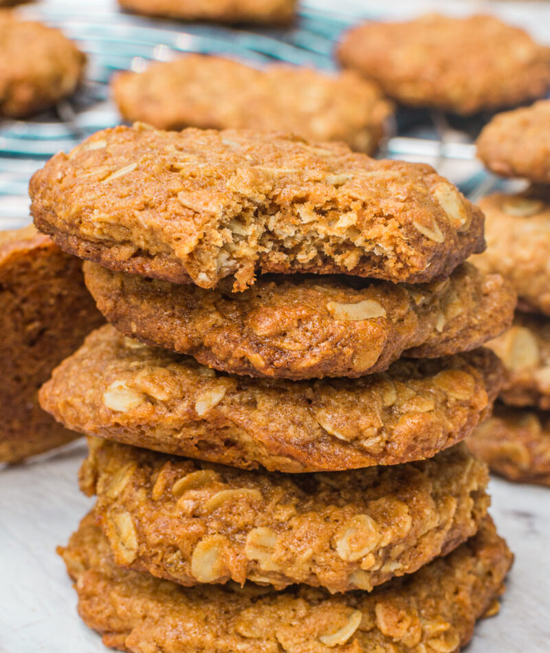 A stack of Anzac biscuits on a marble background with more scattered around