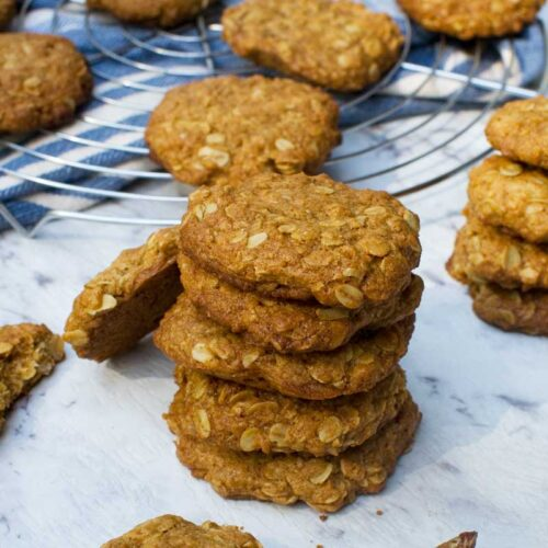 Anzac biscuits in a stack with more in the background