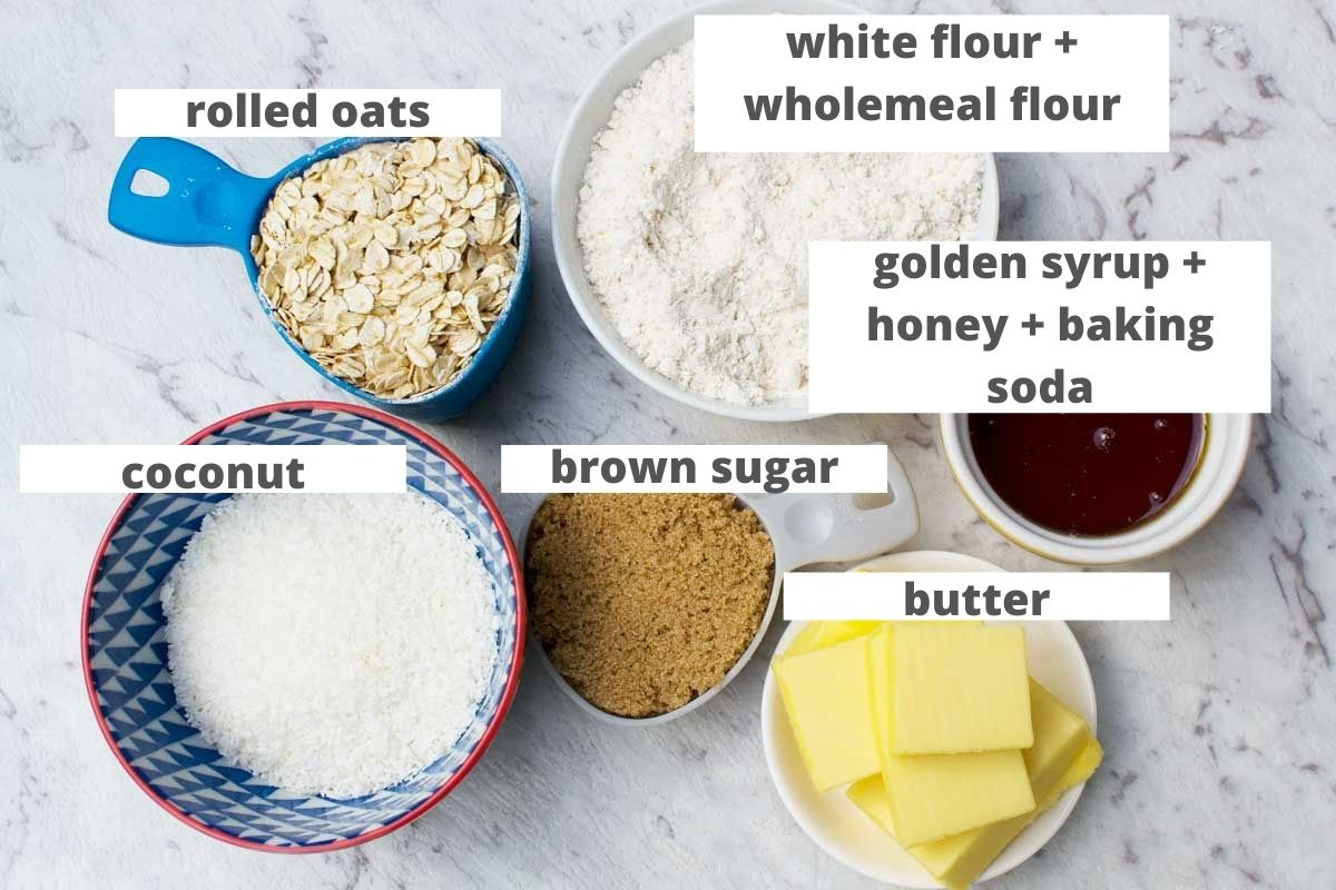 Labelled ingredients to make Anzac biscuits: rolled oats, flour, golden syrup and baking soda, coconut, brown sugar and butter