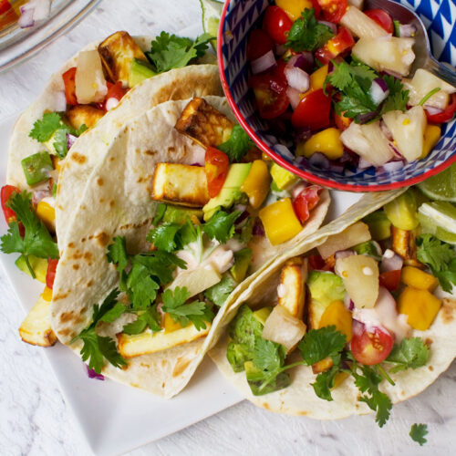 Horizontal image of 3 halloumi tacos with pineapple mango salsa on a white plate with a blue dish of the salsa