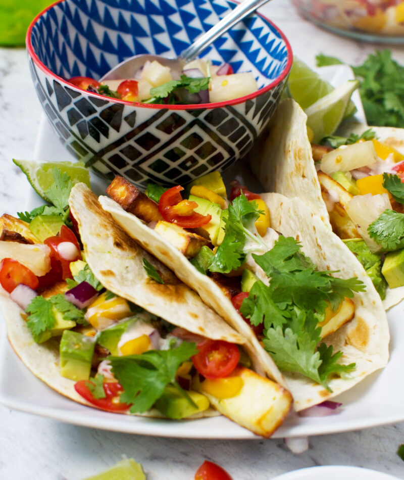 3 halloumi tacos with pineapple mango salsa on a white plate with a bowl of the salsa