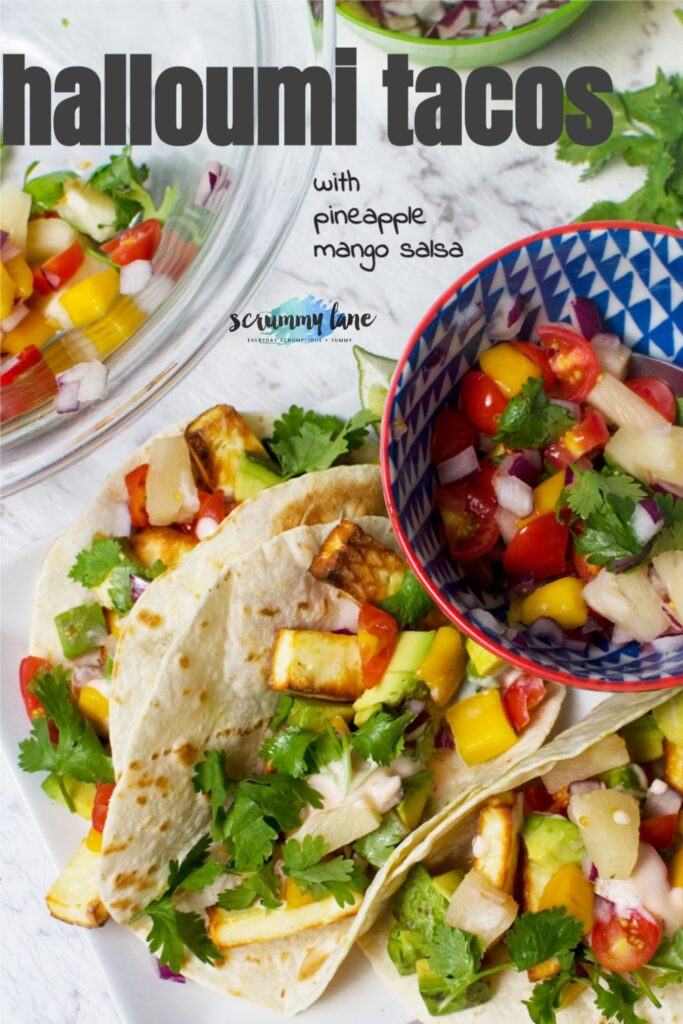 A close up of 3 halloumi tacos with pineapple mango salsa with a grey title on for Pinterest