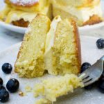 Someone eating a slice of lemon mascarpone cake on a pale beige plate with blueberries with a fork