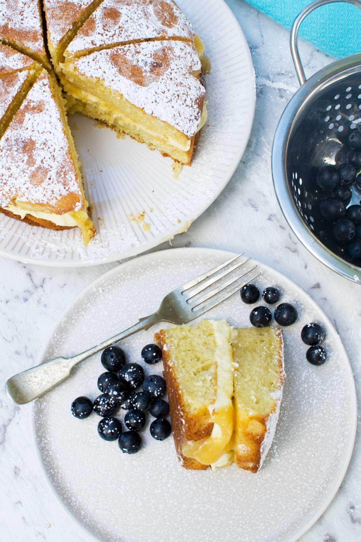 A slice of lemon mascarpone cake on a plate and the rest of the cake on a white plate on a marble background from above