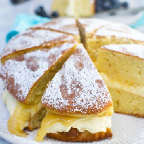 A whole lemon mascarpone cake sliced on a white plate