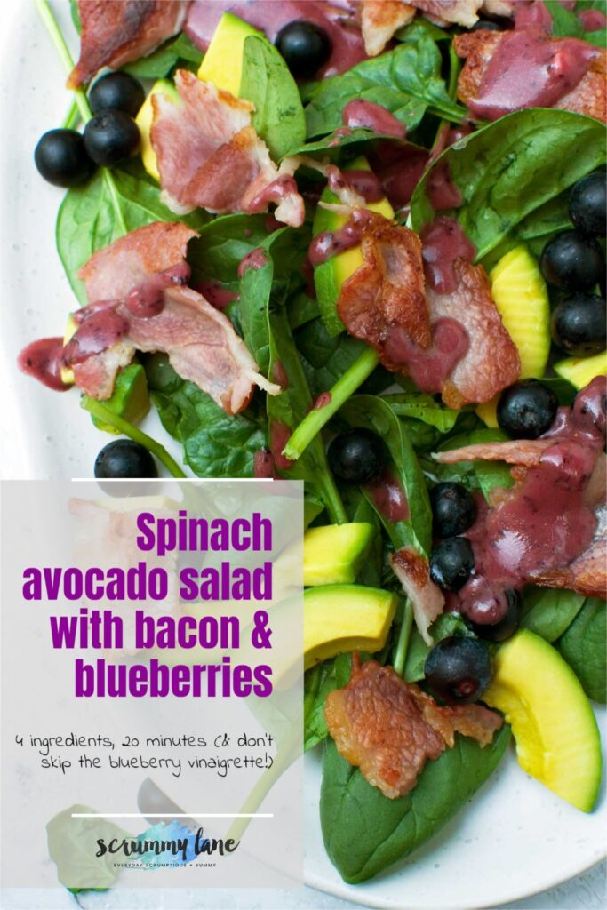 A closeup of a spinach avocado salad with blueberry dressing with a title on it for Pinterest