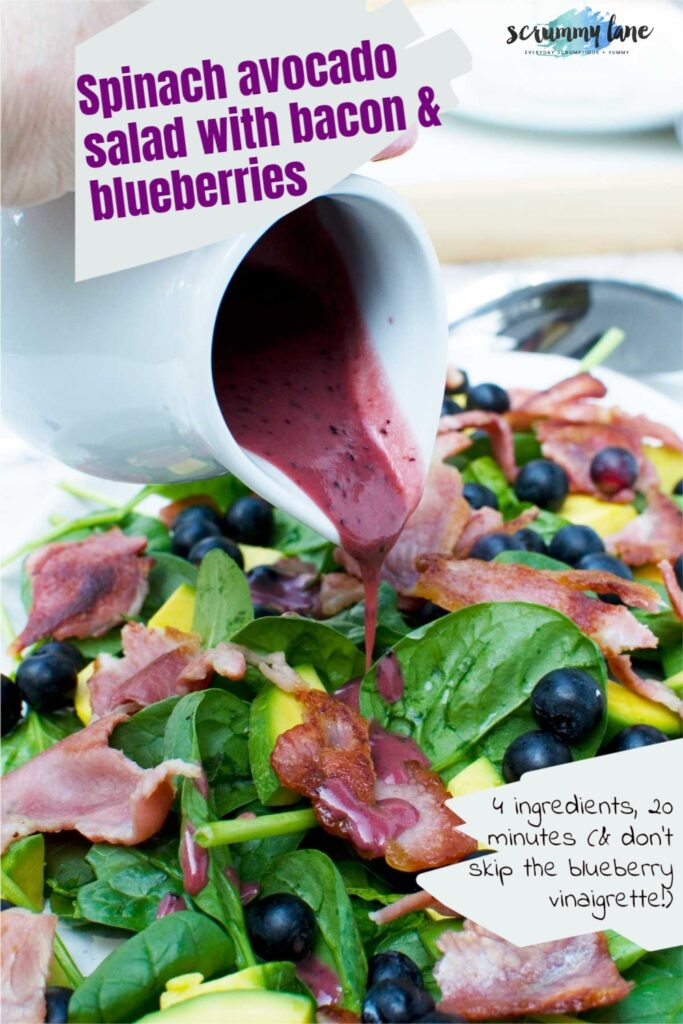 Someone pouring blueberry vinaigrette onto a spinach avocado salad with bacon and blueberries from a white jug and there's a title and subtitle on it