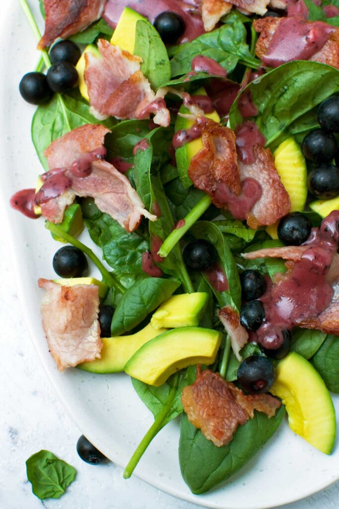 Close up of a spinach avocado salad with bacon and blueberries from above on a white platter