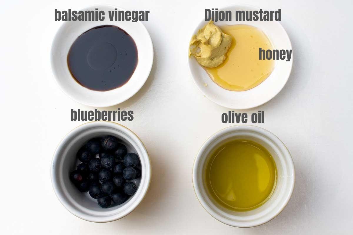 5 labelled ingredients for making blueberry dressing: balsamic vinegar, Dijon mustard, honey, blueberries and olive oil