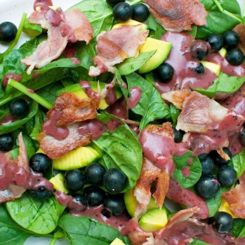 A close-up of a spinach avocado salad with blueberry vinaigrette on it