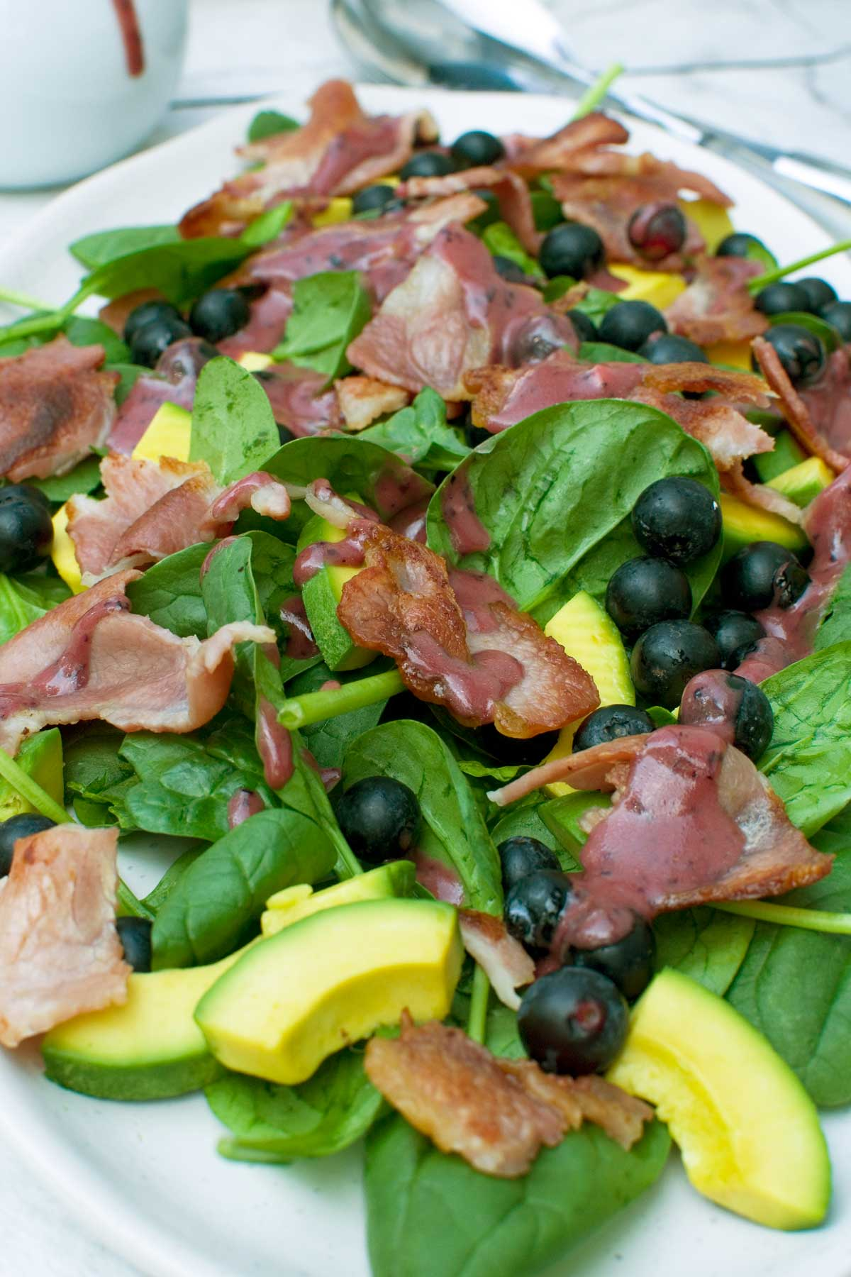 Close up of a blueberry bacon salad with blueberry dressing on it