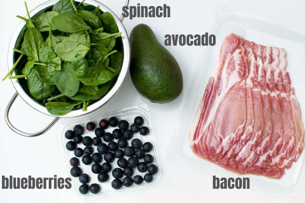 The 4 ingredients to make a spinach avocado salad with bacon and blueberries