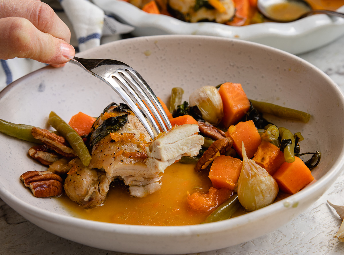 A fork holding up a piece of chicken over a small dish of chicken and sweet potatoes with maple orange sauce