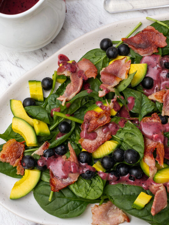 An oval platter of spinach avocado salad with a white jug of blueberry dressing from above on a marble background
